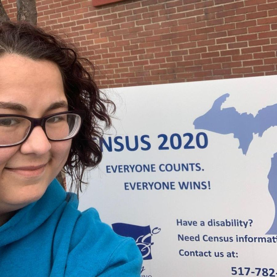 a woman with short dark hair and glasses wearing a blue hoodie smiles as she takes a selfie.  over her shoulder is the census yard sign in front of a brick wall