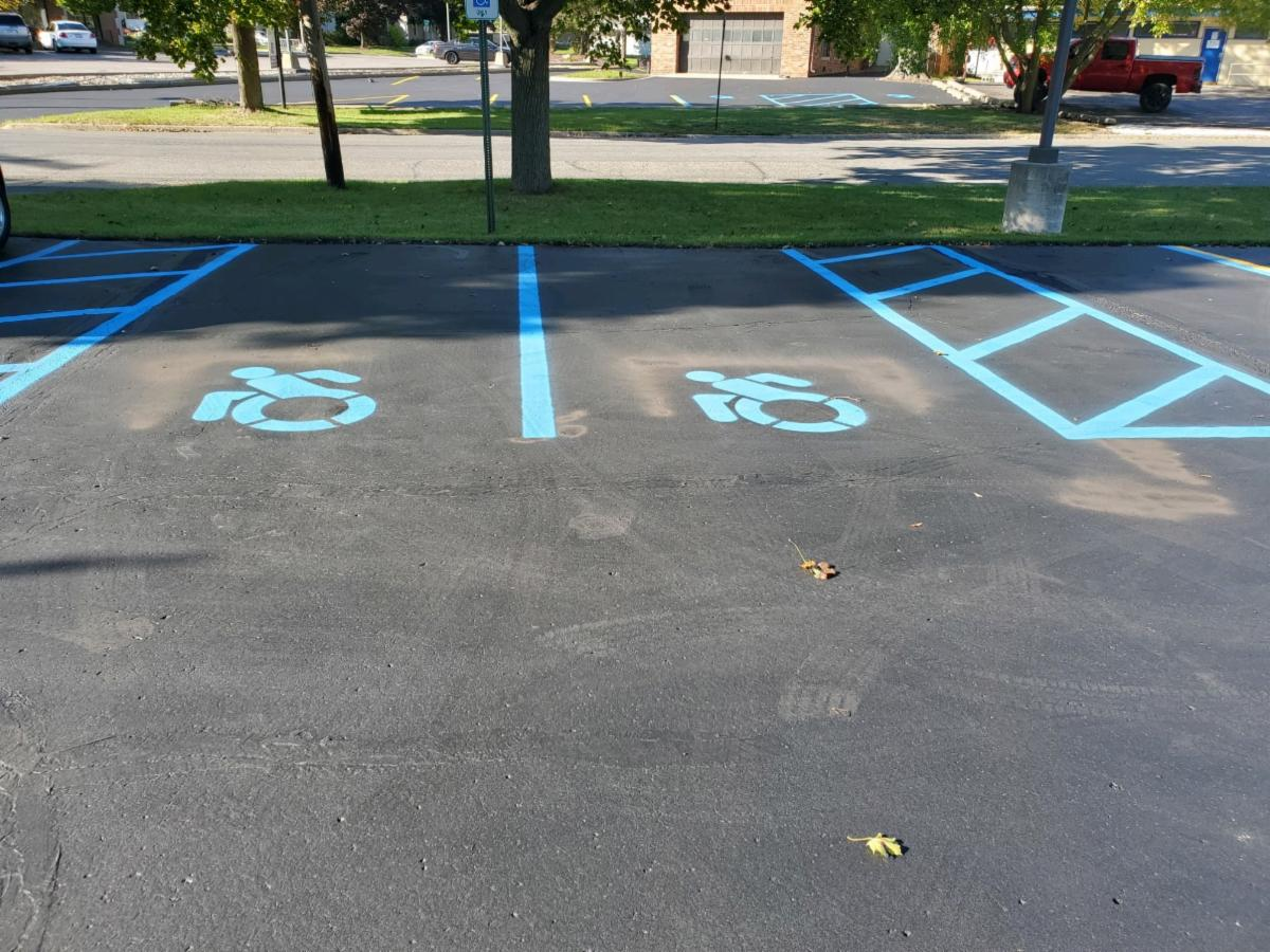 A recently resurfaced parking lot is shown with accessible parking spaces marked by the new design for the international disability sign. they are in light blue paint and show the person in a wheelchair leaning forward to push