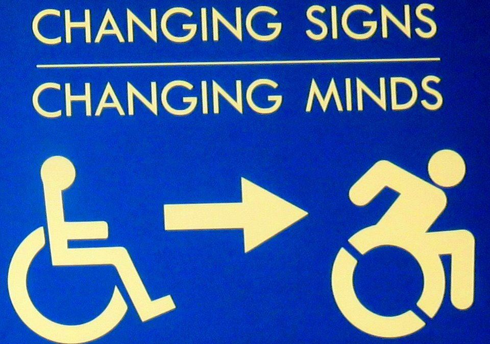 white writing on a blue background that says changing signs changing minds and below that shows the old static logo of disability with an arrow pointing towards the new logo with added motion for disability
