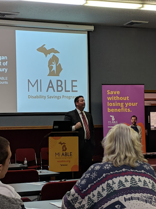 Man in a suit and tie stands in front of a screen that says MI Able.