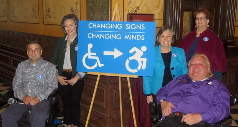 dc employees along sign saying changing signs. changing minds. with current static handicapped logo and newer more dynamic version