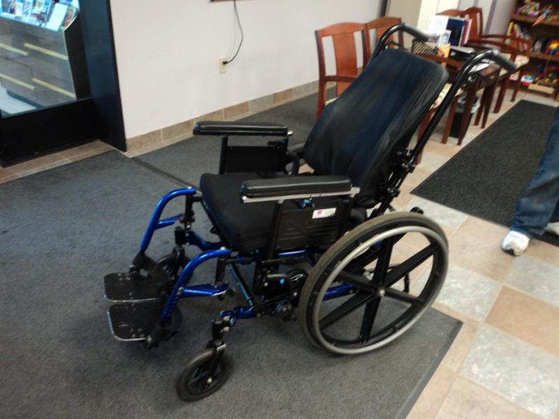a black wheelchair with blue leg rests sits still on a rug over tile floor