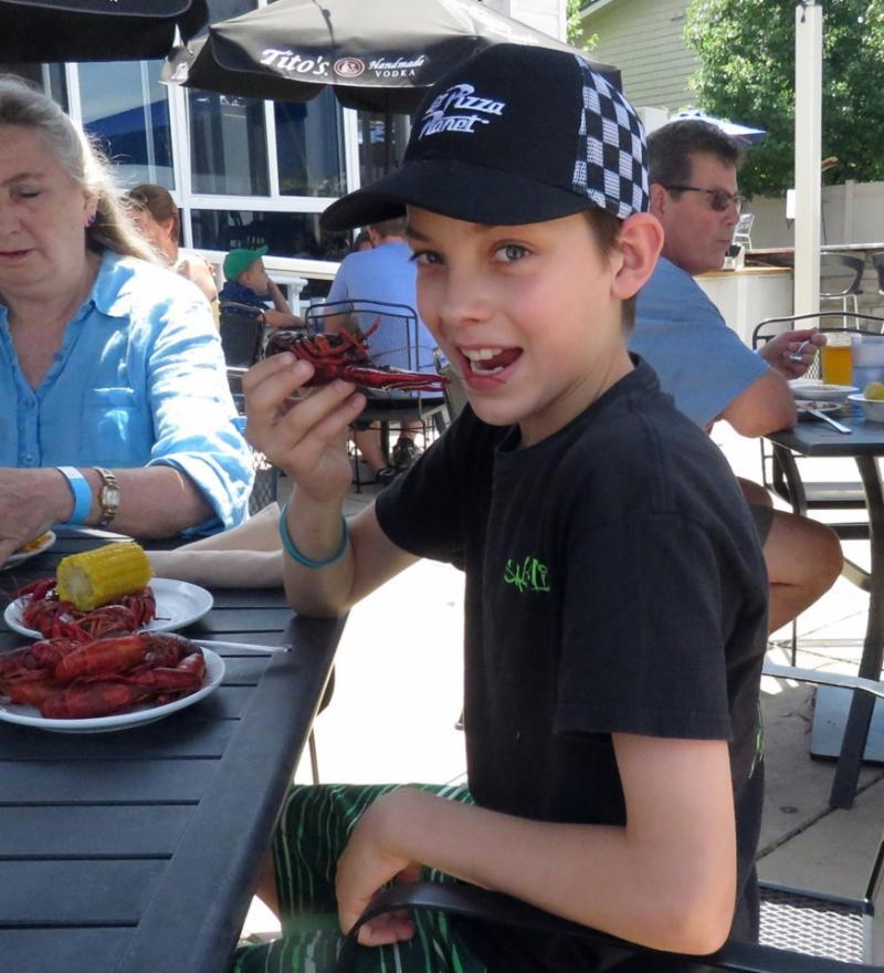 Young kid sitting at a picnic table in black tee shirt and baseball cap holds a crawfish to his mouth pretending to eat it.