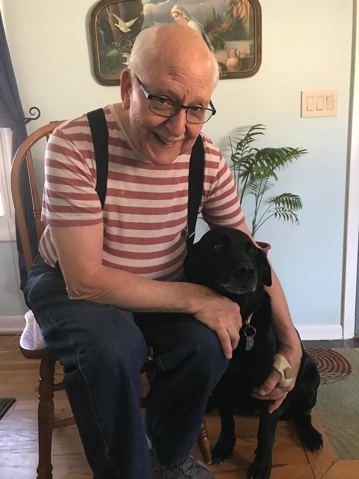 an older man with glasses and wearing  a red and white striped shirt  smiles as he sits in a chair petting a black dog sitting beside him.