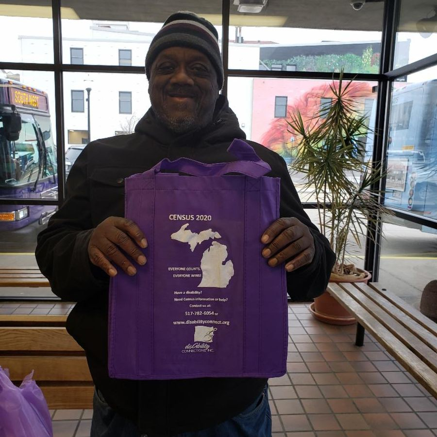 a man standing wearing a ski cap and black jacket holds up in front of his chest a purple reusable tote bag.  the bag shows a white outline of upper and lower michigan and beside it in white writing says Census 2020 Everyone counts. Everyone wins.