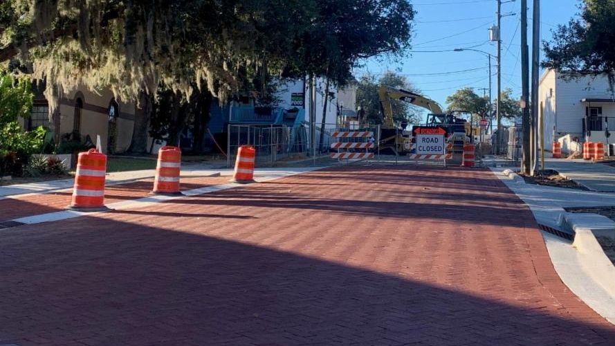 red brick road in foreground, construction signs in background, blue sky above, trees on both sides