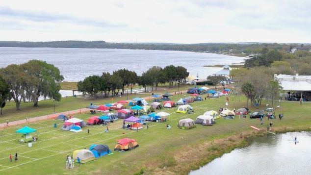 aerial photo of campout tents in grass with lake in background