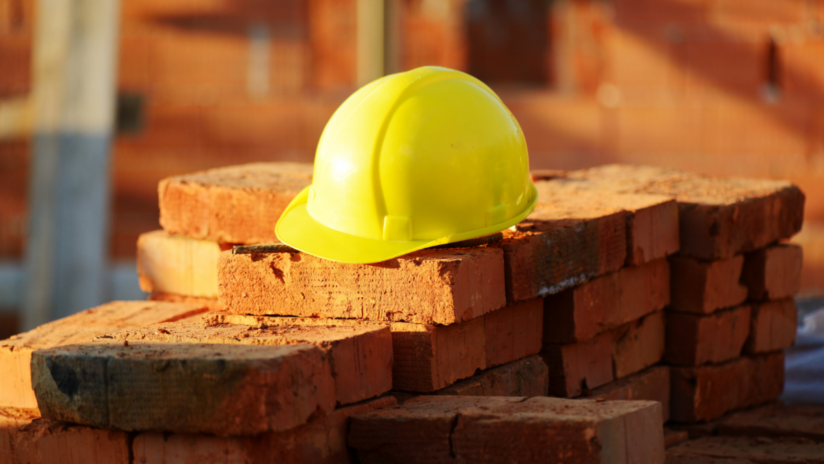 Stacks of red bricks with yellow hard hat on top