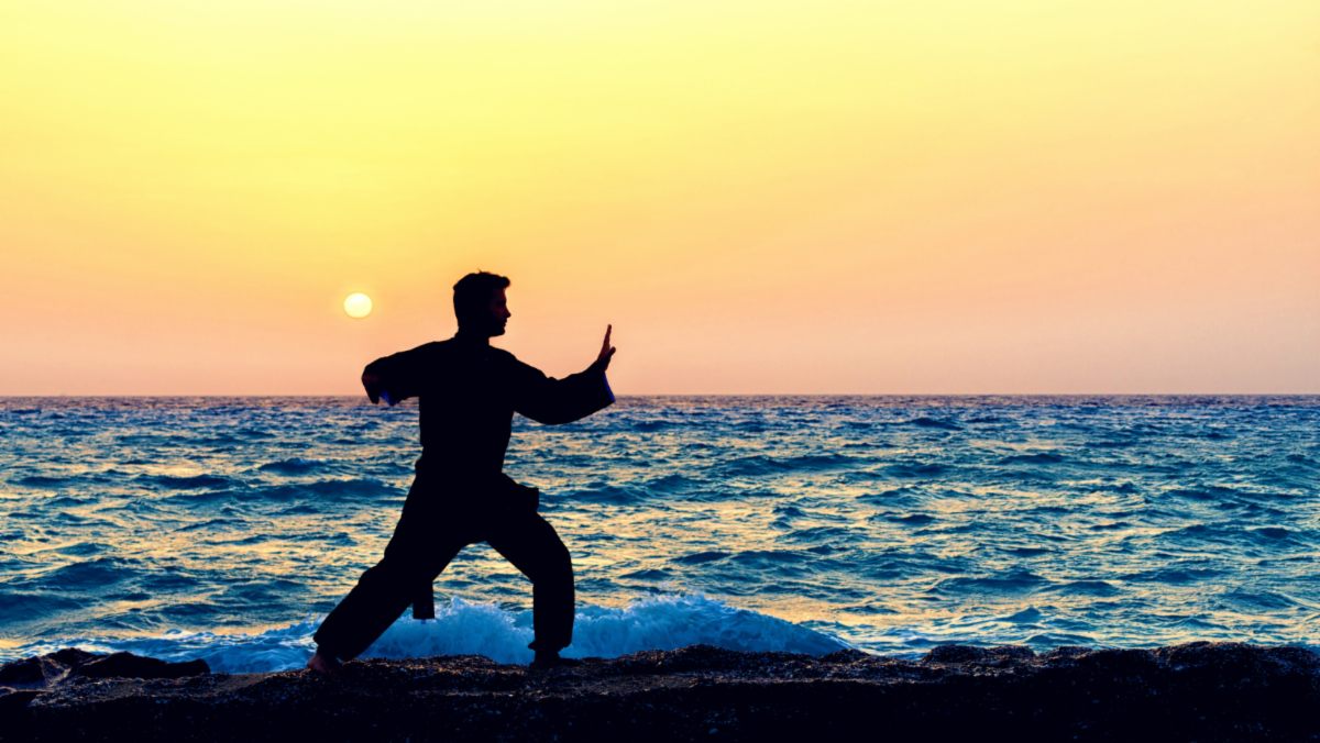 man doing tai chi with ocean and sunset behind him