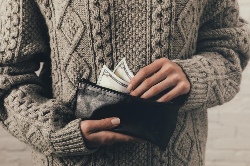 cropped view of woman in sweater holding wallet with dollar banknotes