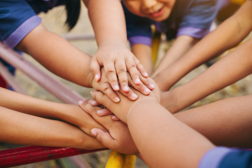 Group of diverse kids hands of together joining for teamwork_ community_  togetherness and collaboration concept.