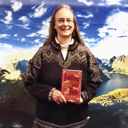Bestselling author Kathleen Ernst holding her Chloe Ellefson mystery  Fiddling With Fate