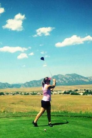 Woman in shorts swinging a golf club with the mountains in the background