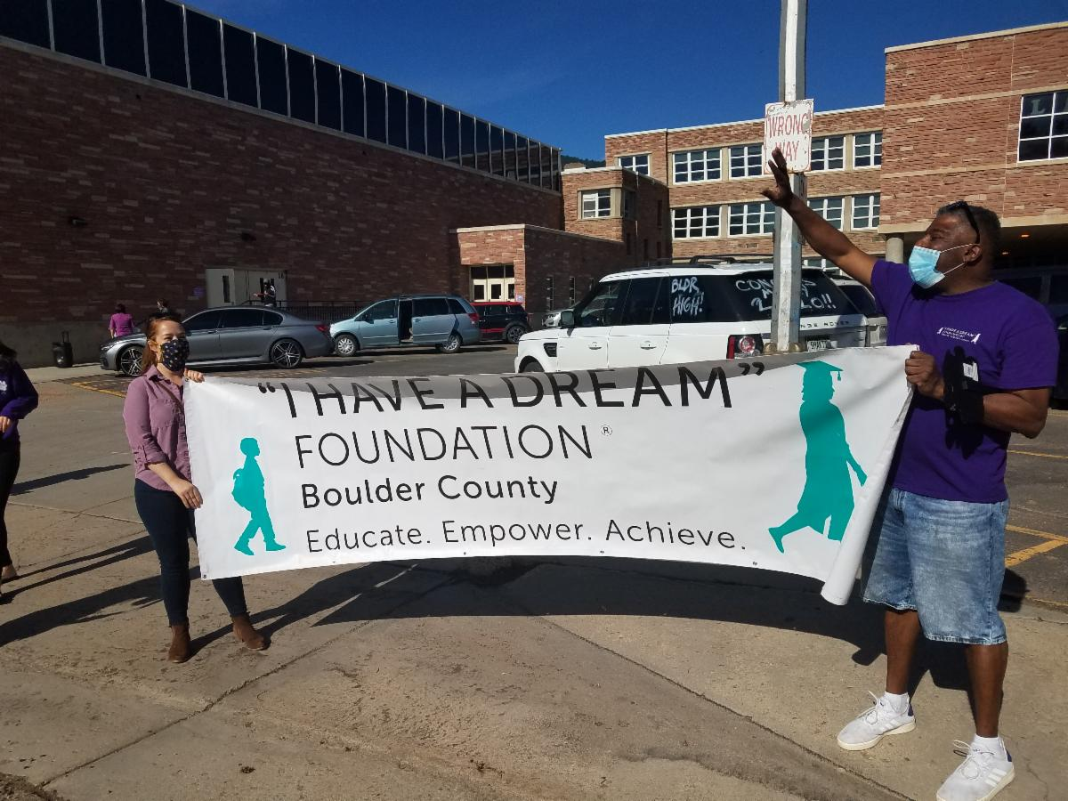 """Phoenix Class Program Director Francisco Mejias and College & Career Director Keelin McGill hold the """"I Have A Dream"""" banner at a socially distanced parade for Boulder High School graduates."""