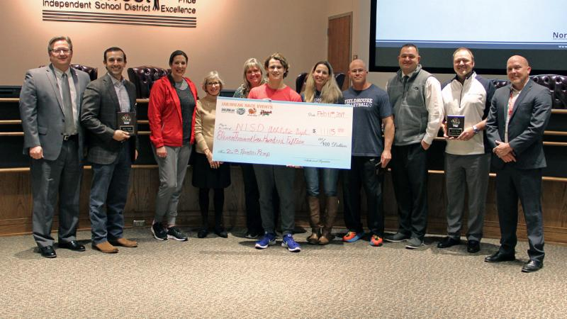 Reindeer Romp sponsors present a check to the district for PE departments