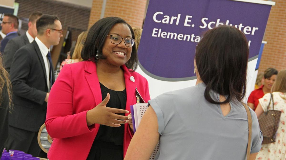 Schluter Elementary School Principal Kasey Rogers talks to a prospective teacher at the 2019 career fair.