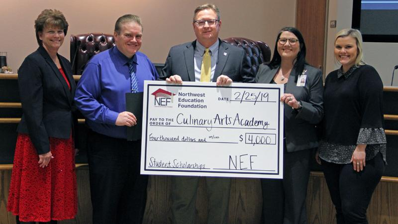 Trustees accept a check from NEF for the Culinary Arts Academy