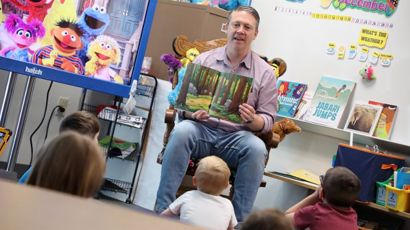 a volunteer reads to children at Lakeview Elementary School