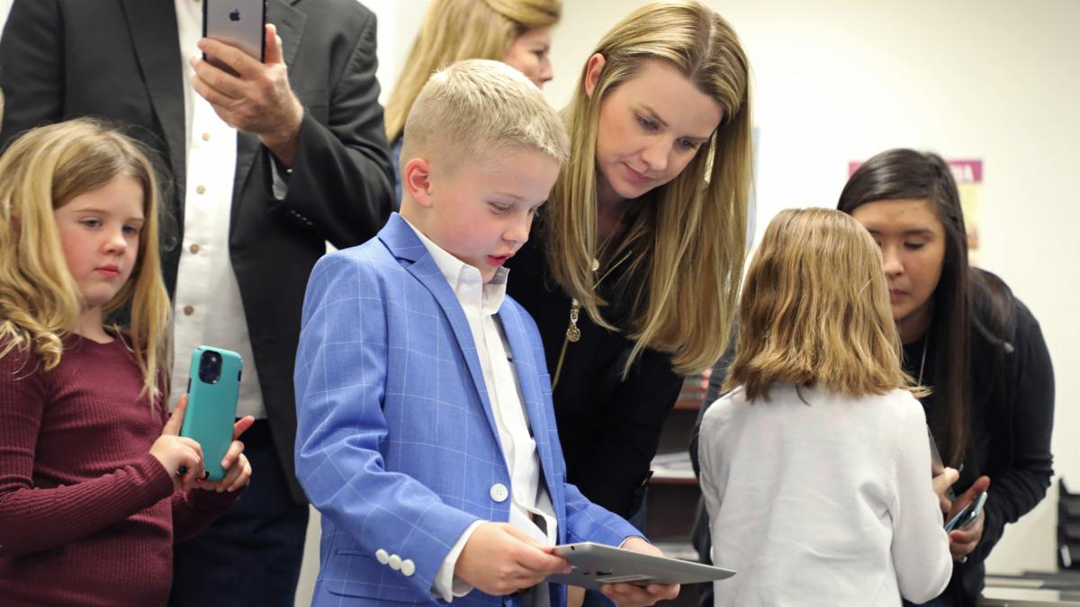 A young male student shows his mom an app to control a robot at Expo