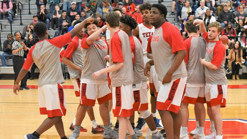 The Northwest Texans boys basketball team break from a huddle