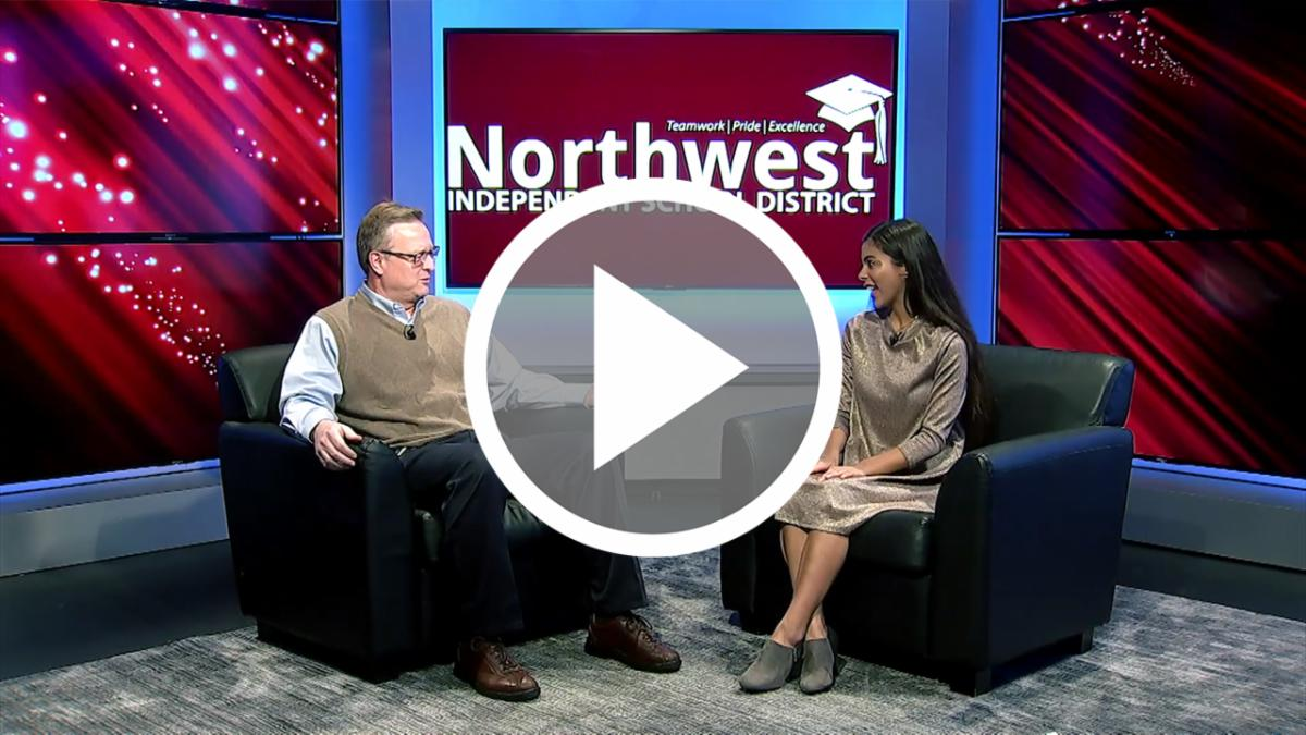 Dr. Ryder Warren sits with NHSTV student anchor Klover Gandy in the NHSTV studio, with an overlay of a button to press to watch the video