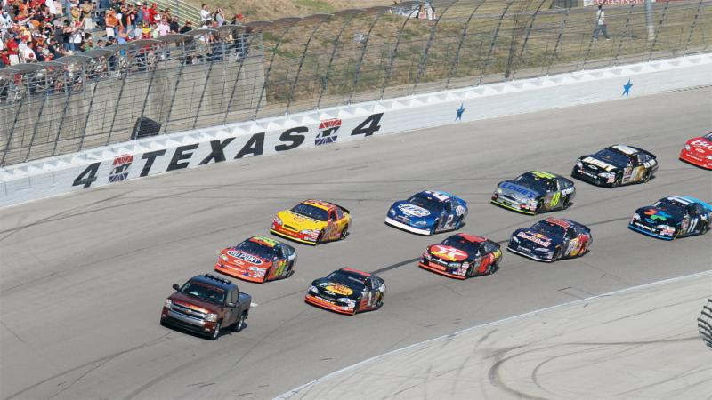 Several cars take part in a NASCAR race at Texas Motor Speedway