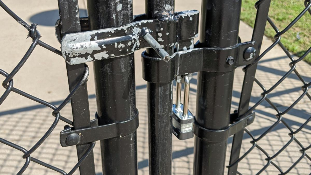 A locked gate to an athletic complex.
