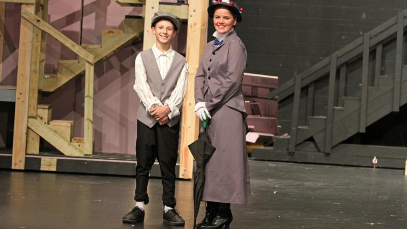Students playing Burt and Mary Poppins pose for a photo