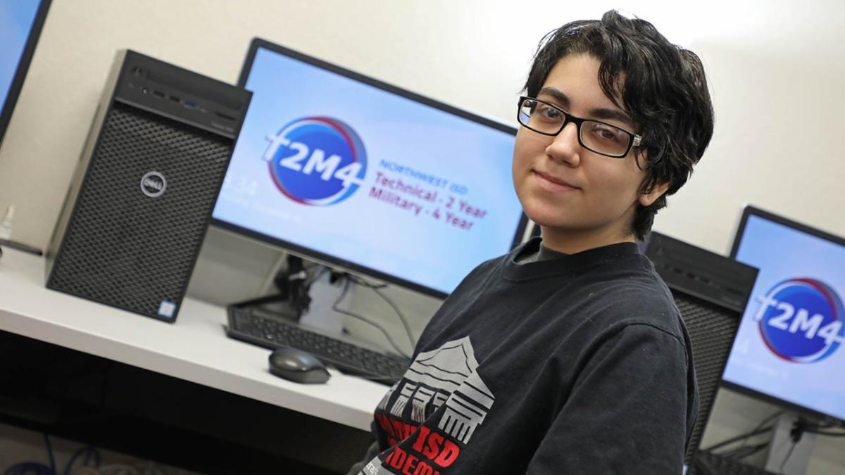 Steele student Alex Prince poses in front of computers at his school.