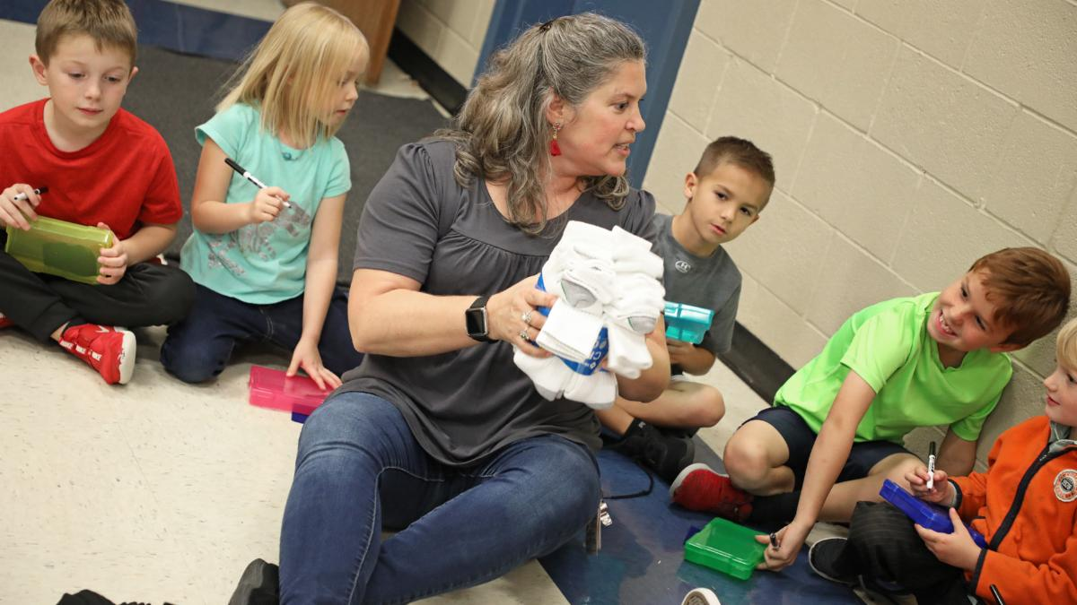 Justin first-grade teacher Susan Logan shows students a group of socks to sort.