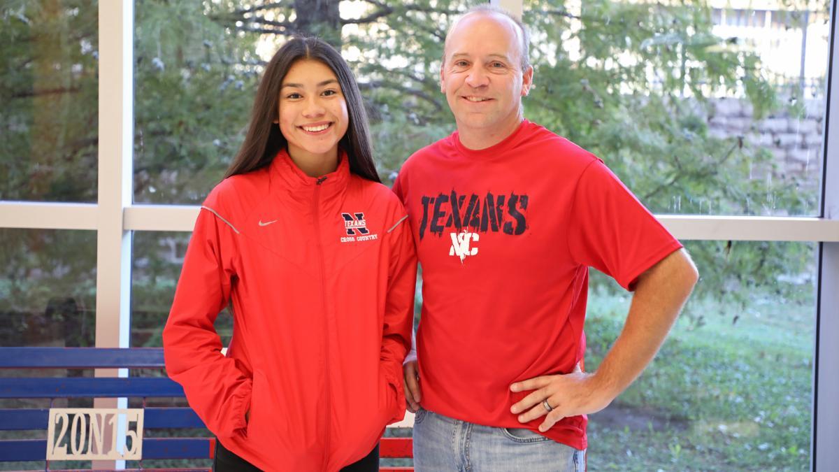 Kayla Martinez poses with coach Burke Binning at Northwest High School in XC attire
