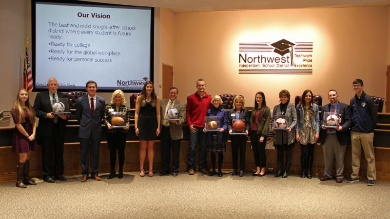 Trustees receive athletic balls presented by student-athletes for being the district's all-star team.