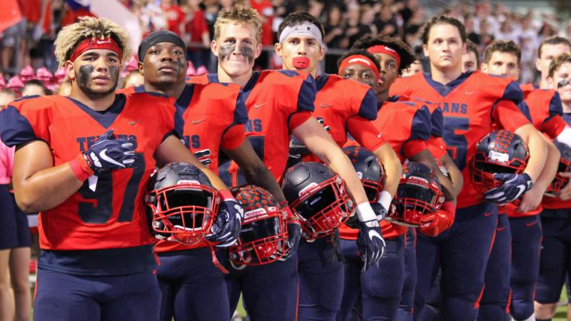 The Texan football team stands for the National Anthem