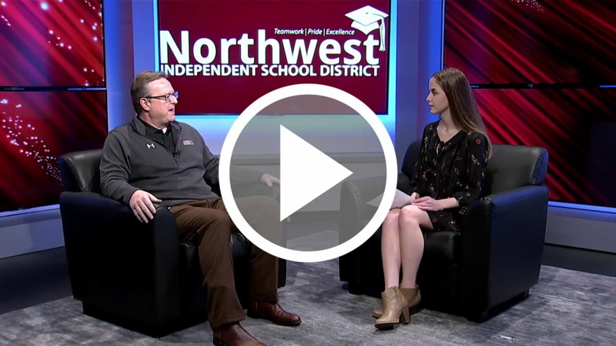 Dr. Warren sits in NHSTV studios with a student interviewer