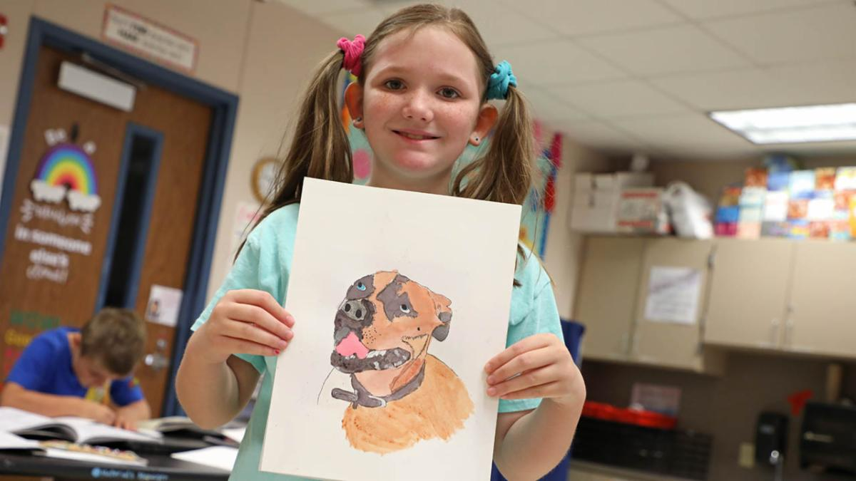 A Justin Elementary School student poses with her painting of a dog up for adoption