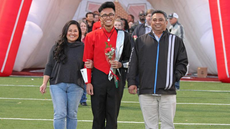 A band member poses for a senior night photo with his parents