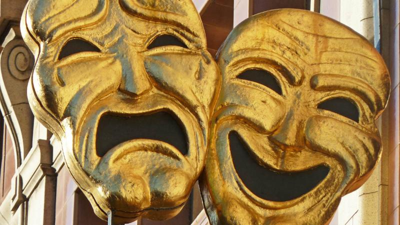 A photo of two theatre tragedy and comedy masks