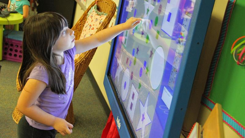 A pre-K student interacts with a touchscreen monitor