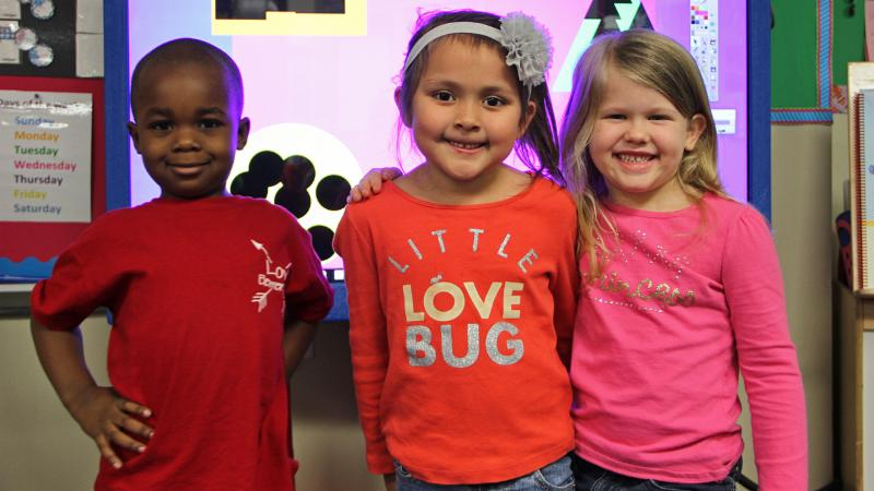 Three pre-K students posing for a photo