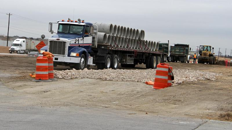 Trucks move materials at the U.S. Rotue 287 ramp project