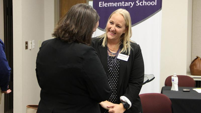 Amy Howell talks to a potential employee at the HR Teacher Career Fair