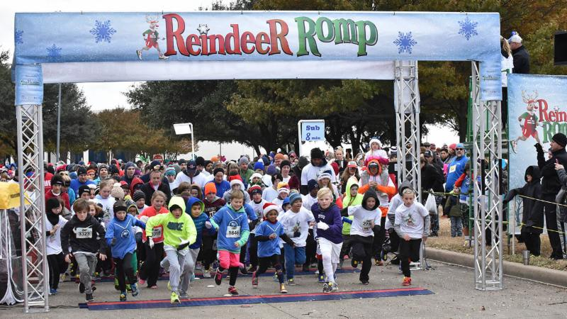 A large group of participants begin the Reindeer Romp, crossing the start/finish line