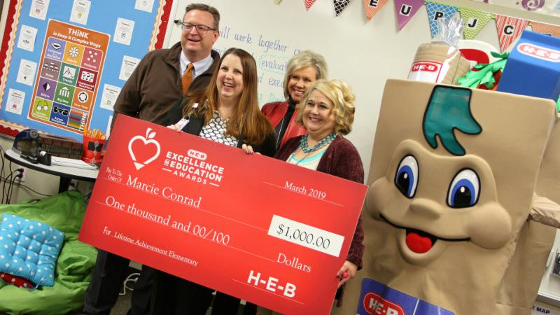 Marcie Conrad poses for a photo with school and district officials