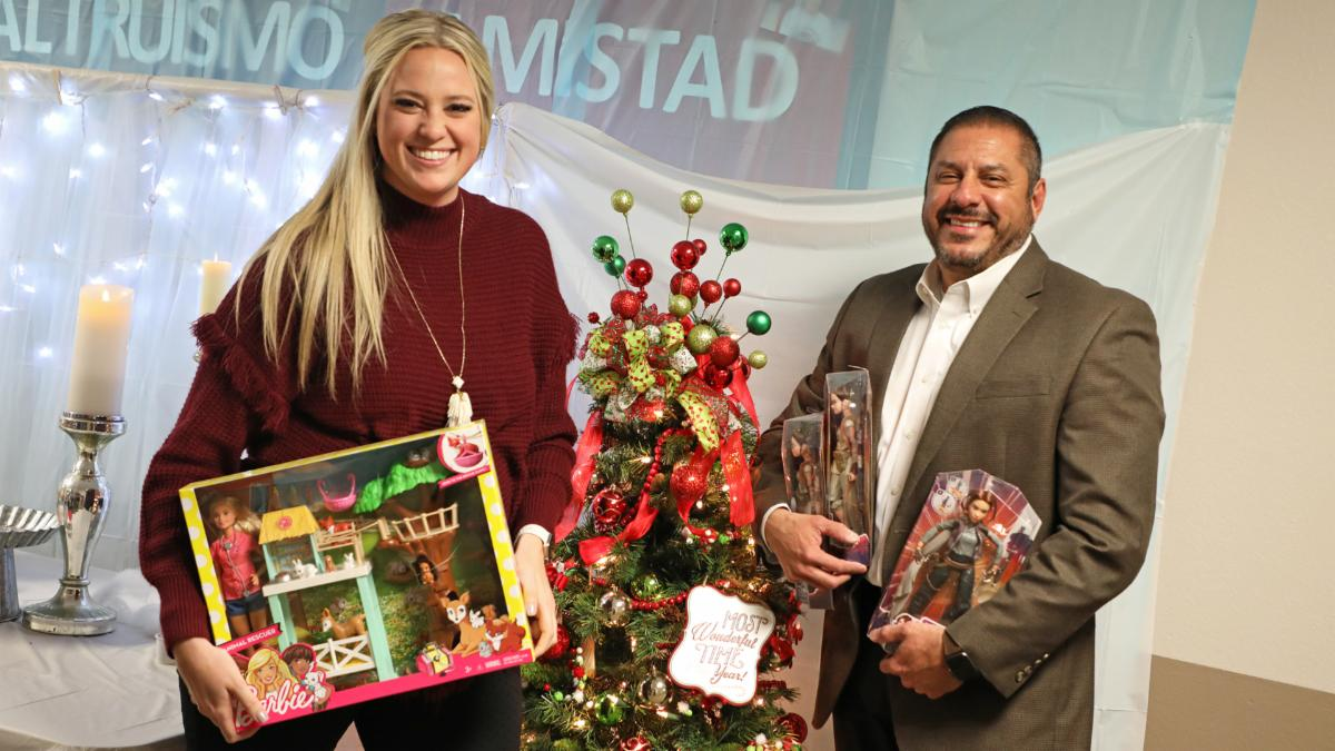 Two members of the community relations team hold gifts for Angel Tree children