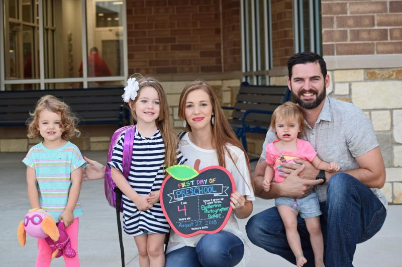 A family poses for a first-day photo in front of Curtis Elementary