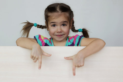 Cute 5 years old girl with funny pigtails pointing with her fingers down on white board_ space for copy_ advertising and announcement concept_ studio shot over white background