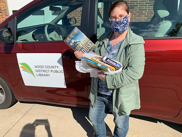 Librarian Katherine Lawn stand by library van with books selected for a home delivery stop.