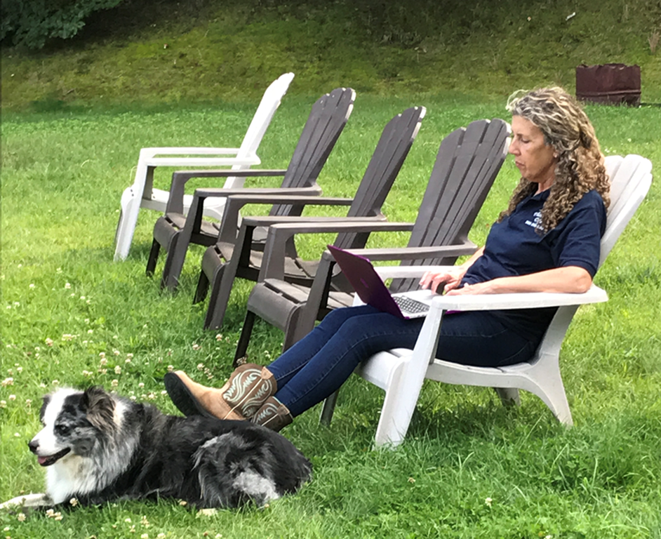 woman sitting outside in a lawn chair with a laptop and her feet propped up on a dog