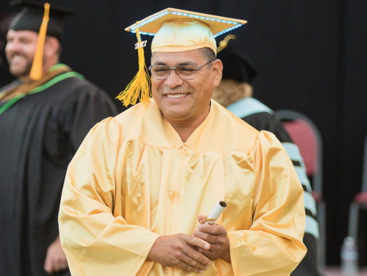 Photo of a male graduate in cap and gown holding a scroll of paper