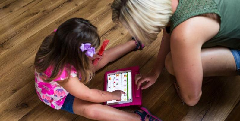 Young girl sits on the floor holding a popsicle in one hand and using the other hand to tap a communication app on a tablet screen. Her mother leans over_ also pointing to the tablet screen.